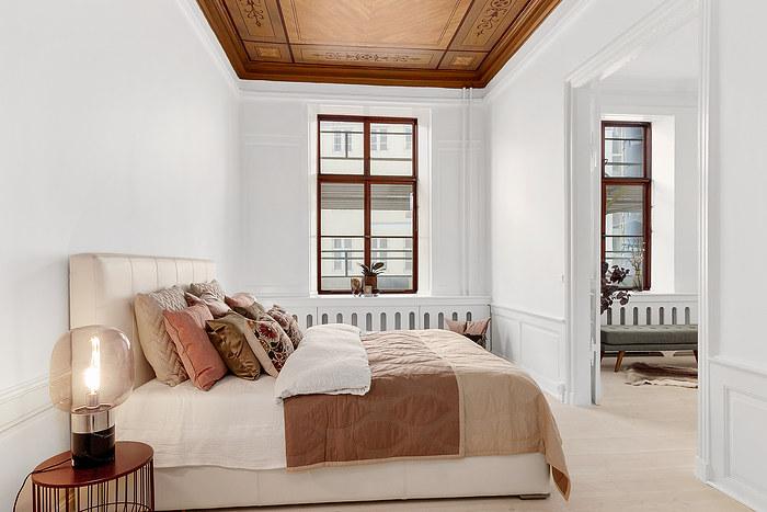 Komplet indretning af Salesstyling i herskabslejlighed. Soveværelset er i hvid, rosa og brun. Hyggelige puder og smukt malet loft.